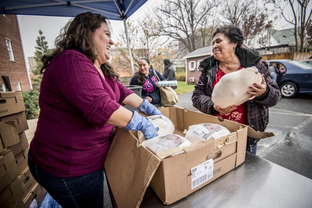 A woman in a fuchsia shirt is rearranging frozen turkeys in a cardboard box. Another woman in a black jacket is holding 1 frozen turkey.